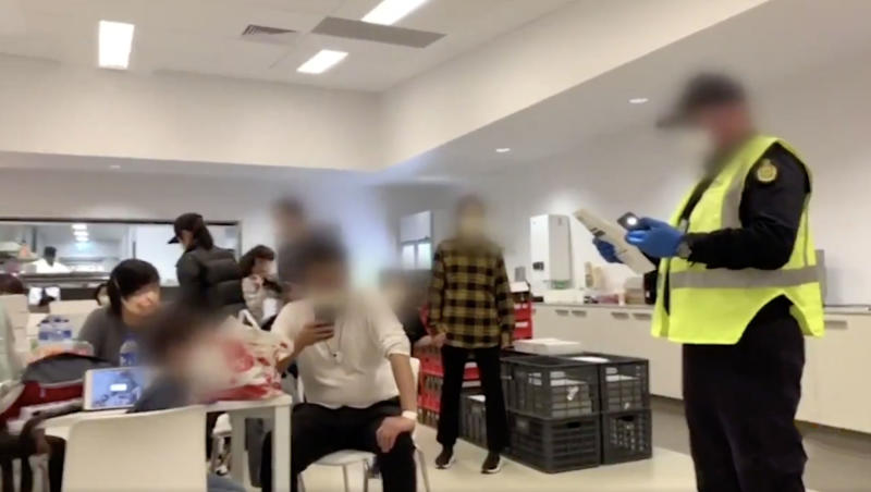 An official instructs Australians in a communal kitchen area within the centre. Source: 7News