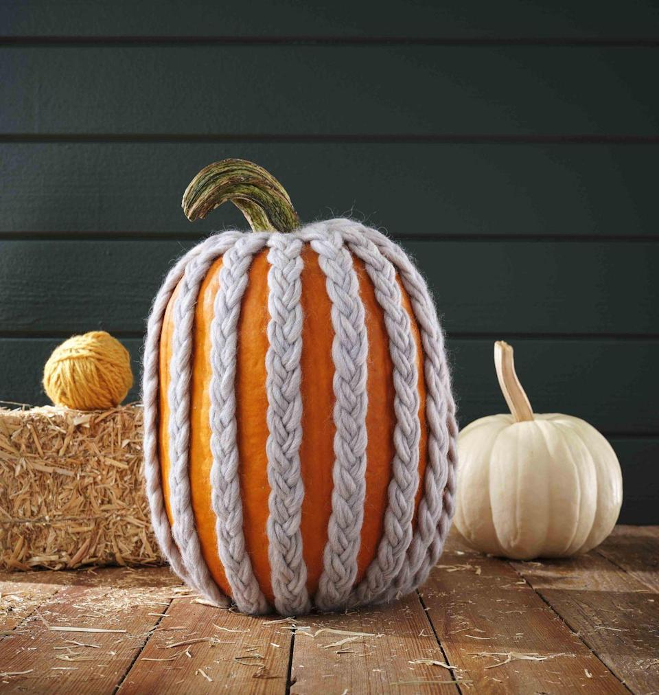 <p>Braided lengths of soft yarn will keep you pumpkin warm come October 31. <strong><br></strong></p><p><strong>Make the pumpkin:</strong> Glue four strands of yarn together and to the top of the pumpkin just below the stem with hot-glue. Braid stands together, using two strands per plait. Glue braid to the bottom of the pumpkin with hot-glue. Repeat, spacing braids about one-inch apart, until covered. </p>