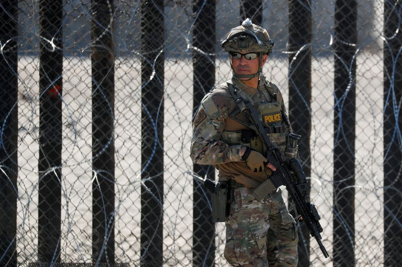 FILE PHOTO: An armed U.S. Customs and Border Patrol agent stands watch at the border fence next to the beach in Tijuana, at the Border State Park in San Diego, California
