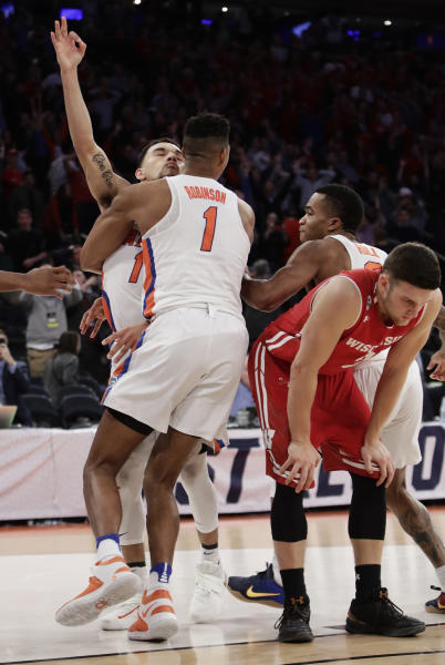 Florida forward Devin Robinson (1) hugs guard Chris Chiozza (11) after Chiozza hit the game winning shot in overtime against Wisconsin at an East Regional semifinal game of the NCAA men's college basketball tournament, Saturday, March 25, 2017, in New York. (AP Photo/Frank Franklin II)