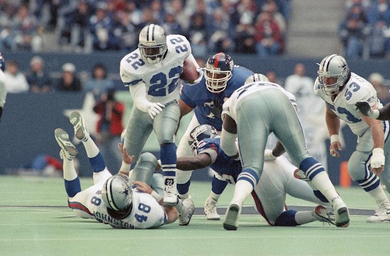 Dallas Cowboys running back Emmitt Smith (22) jumps over teammate Daryl Johnston (48) for a six-yard gain despite the efforts of New York Giants Stacy Dillard (71) and Myron Gyton (29) in the first quarter on Sunday, Nov. 7, 1993 in Irving, Texas. (AP Photo/Ron Heflin)