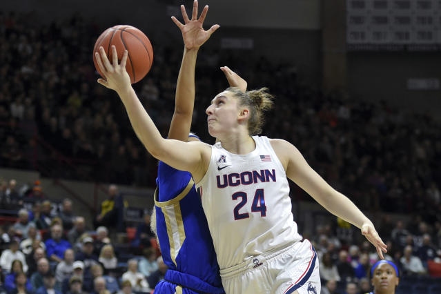 FILE - In this Sunday, Jan. 19, 2020, file photo, Connecticut's Anna Makurat (24) shoots during the first half of an NCAA college basketball game against Tulsa, in Storrs, Conn. Makurat, from Poland, is one of more than 20,000 foreign athletes currently competing at NCAA schools, according to the organization. With competition canceled across all NCAA divisions because of the new coronavirus, many of those athletes face a dilemma. Their campuses are shut down, but the coronavirus situation in their homeland may be worse than it is in the United States. (AP Photo/Stephen Dunn, File)