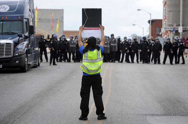 PHOTO: A protester with a police vest faces members of the Baltimore Police Department, April 27, 2015, during unrest following the funeral of Freddie Gray in Baltimore. (Jerry Jackson/The Baltimore Sun via AP, FILE)