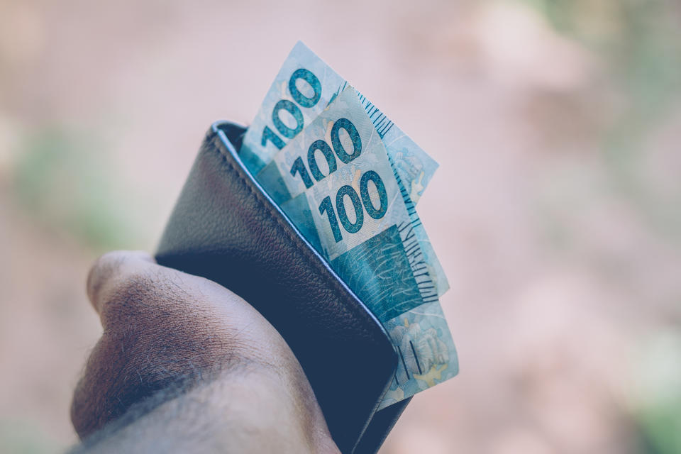 Money from Brazil. Real notes, Brazilian currency inside a black wallet. Concept of finance, economy and wealth.