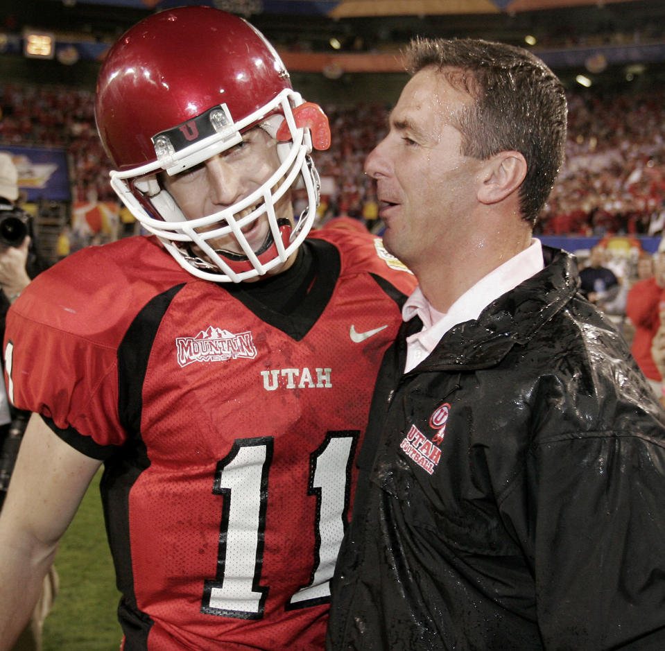 Utah quarterback Alex Smith (11) celebrates with head coach Urban Meyer (R) after defeating the University of Pittsburgh 35-7 in the 2004 Fiesta Bowl. Utah finished the season 12-0. (REUTERS/Jeff Topping)