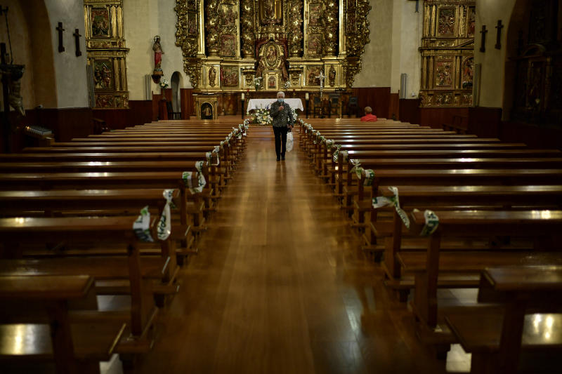 A Devotee wearing a face mask to protect against the coronavirus leaves the church in Lumbier, northern Spain, Sunday, June 7, 2020. The traditional Trinity Pilgrimage was cancelled due to the coronavirus outbreak. (AP Photo/Alvaro Barrientos)