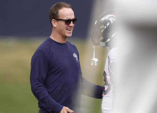 Retired Denver Broncos quarterback Peyton Manning greets former teammate Von Miller during a combined NFL football training camp with the San Francisco 49ers at the Broncos' headquarters Friday, Aug. 16, 2019, in Englewood, Colo. (AP Photo/David Zalubowski)