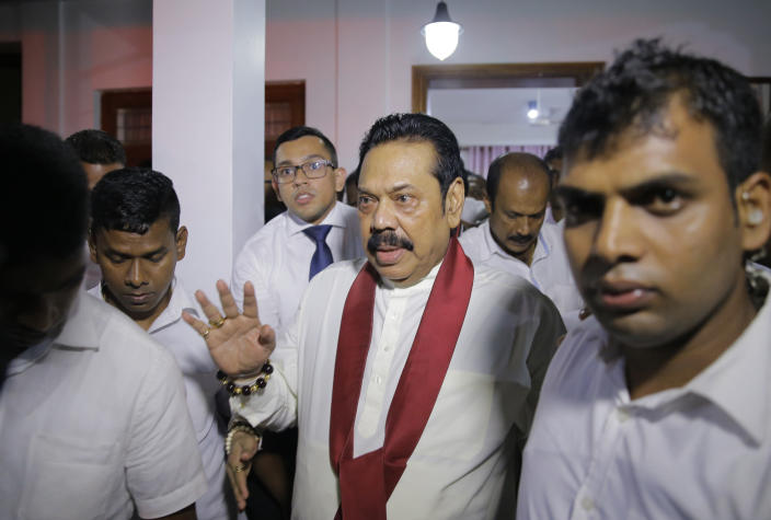 Newly appointed Sri Lankan Prime Minister Mahinda Rajapaksa, center, leaves a Buddhist temple after meeting his supporters in Colombo, Sri Lanka, Friday, Oct. 26, 2018. Sri Lankan President Maithripala Sirisena has sacked the country's prime minister and replaced him with a former strongman, state television said Friday. (AP Photo/Eranga Jayawardena)
