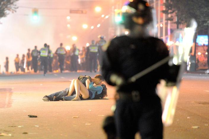 <p>Riot police walk in the street as a couple kiss on June 15, 2011 in Vancouver, Canada. Vancouver broke out in riots after their home team lost in Game Seven of the Stanley Cup Finals. </p>