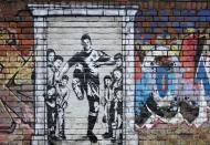 A mural of England soccer player Marcus Rashford kicking down the door of number 10 Downing Street appears on Manchester Canal in Manchester