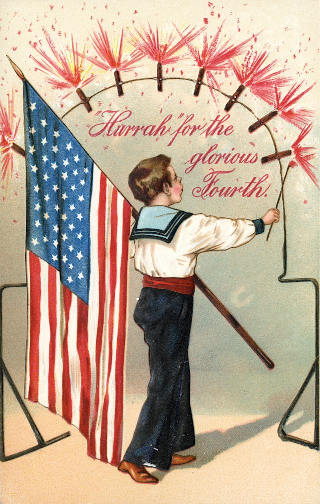 <p>A color lithograph postcard, circa 1915, shows a young boy dressed in a sailor's suit carrying an American flag over his left shoulder. He is lighting firecrackers arranged in a semi-circle to celebrate the 4th of July. Accompanying copy states 'Hurrah for the glorious Fourth.' (Photo: Transcendental Graphics/Getty Images) </p>
