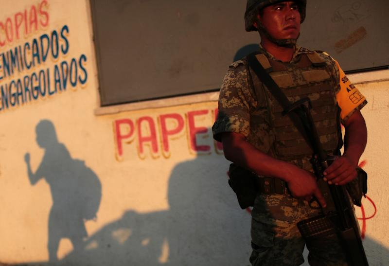 A soldier stands guard outside a school in Acapulco, Mexico, during a security operation to protect teachers and students from gangs demanding extortion payments