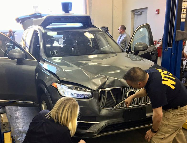 FILE PHOTO: U.S. National Transportation Safety Board (NTSB) investigators examine a self-driving Uber vehicle involved in a fatal accident in Tempe, Arizona, U.S., March 20, 2018. National Transportation Safety Board/Handout via REUTERS
