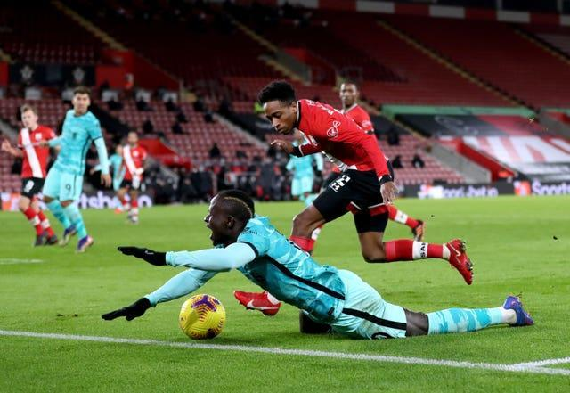 Liverpool forward Sadio Mane falls in the penalty area under a challenge from Southampton's Kyle Walker-Pieters