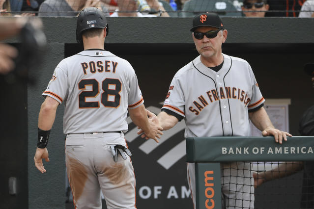 San Francisco Giants' Buster Posey (28) is greeted by manager Bruce Bochy, right, after he scored during the fifth inning of a baseball game against the Baltimore Orioles, Saturday, June 1, 2019, in Baltimore. (AP Photo/Nick Wass)