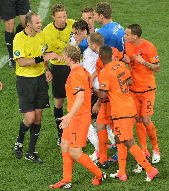 German midfielder Mesut Oezil (C) argues with Dutch forward Dirk Kuyt (foreground L) during the Euro 2012 championships football match the Netherlands vs Germany on June 13, 2012 at the Metalist Stadium in Kharkiv.  AFP PHOTO / SERGEI SUPINSKYSERGEI SUPINSKY/AFP/GettyImages