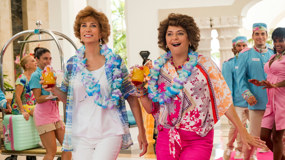 Kristen Wiig and Annie Mumolo as Barb and Star, wearing floral outfits and leis.