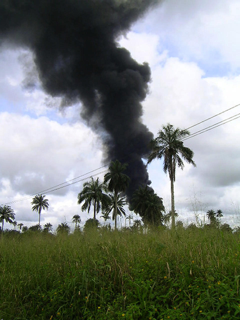 FILE - In this file photo dated Tuesday, Oct. 12, 2004, smoke rises from an oil pipeline fire near the village of Goi in Nigeria. A Dutch appeals court Friday Feb. 12, 2021, has ordered energy giant Shell's Nigerian subsidiary to compensate farmers in two villages including Goi for damage to their land caused by a pair of oil leaks more than 15 years ago. (AP Photo)