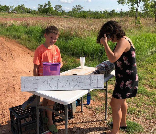 Andrew Jazyschyn, 10, serves a thirsty customer outside his family's home in the Northern Territory. Source: Philip Jazyschyn