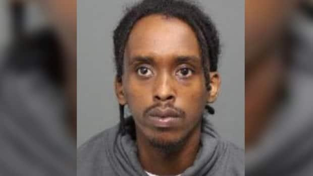 Haybe Farhan Aden, 26, is wanted in connection with a July 4 shooting in Lowertown that killed 20-year-old Tyson Ndongozi and injured an 18-year-old man. (Ottawa Police Service - image credit)