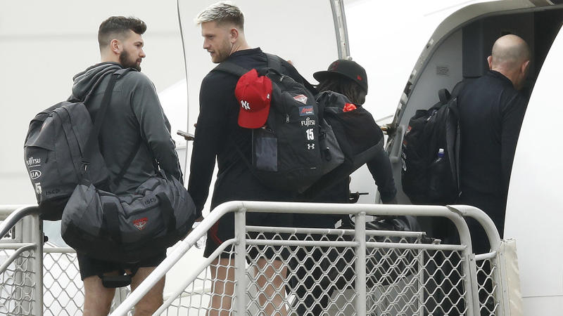 Essendon Bombers players, pictured here boarding a flight out of Melbourne Airport.