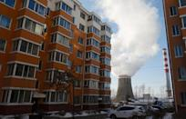 Smoke billows from a cooling tower of a thermal power plant near residential buildings in the coal city of Hegang