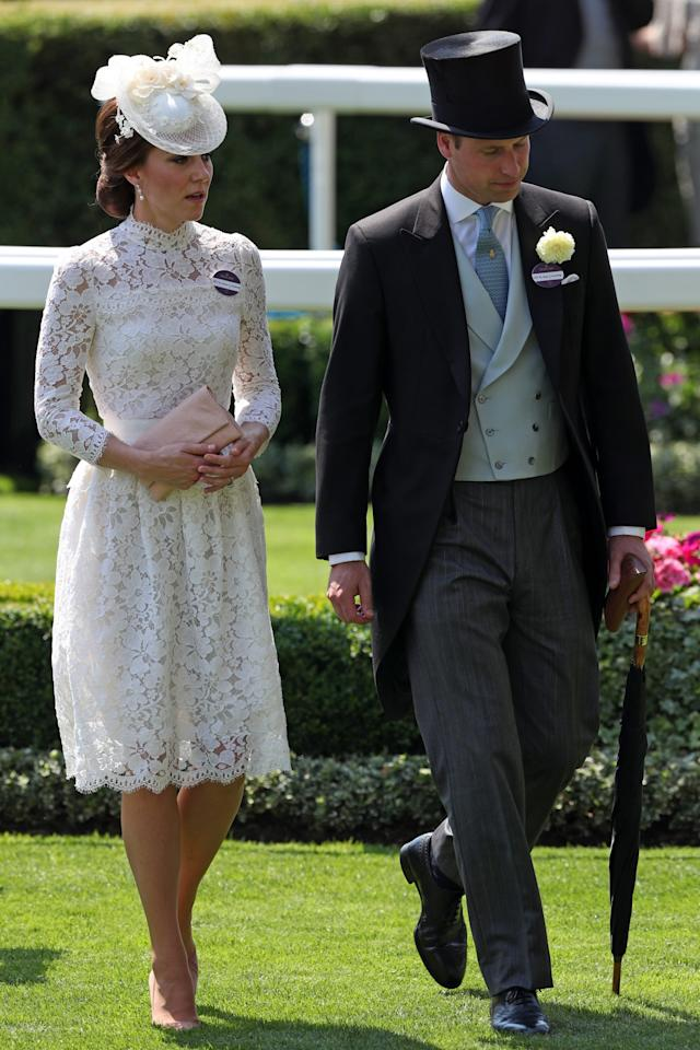 <p>Kate and William arrived at the 2017 race event in a very similar look to last year. The Duchess donned a white lacy dress by Alexander McQueen with a pearl-embroidered hat while William went for a black-and-grey morning suit.<br /><i>[Photo: PA]</i> </p>