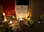 Candles and flowers are arranged at a vigil for Winston Boogie Smith Jr. early on Saturday, June 5, 2021. Authorities say Smith, wanted on a weapons violation, fired a gun from inside his vehicle before he was fatally shot by members of a federal task force as they were trying to arrest him. (AP Photo/Christian Monterrosa)