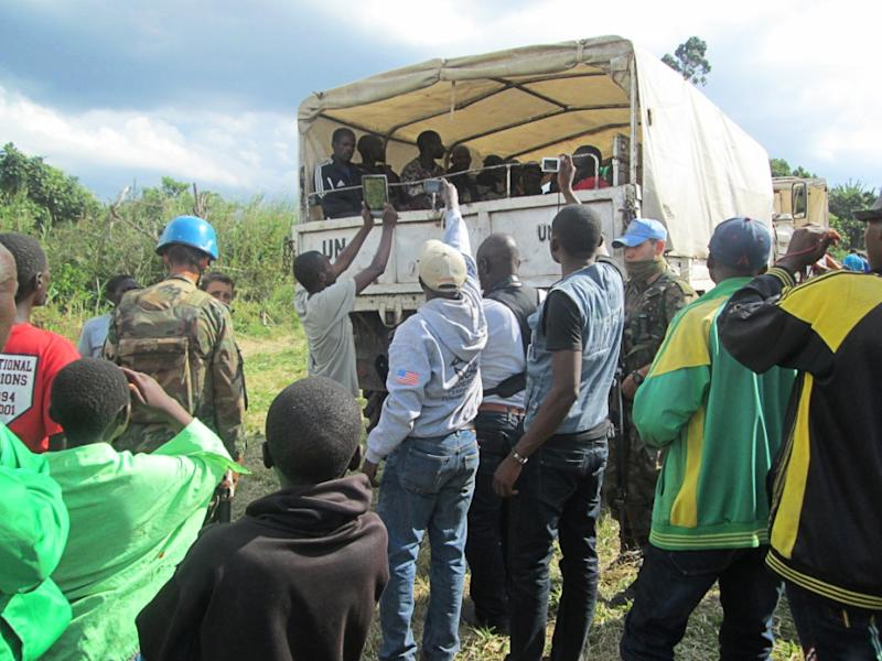 UN peacekeepers and residents look at members of the Democratic Forces for the Liberation of Rwanda rebel group boarding a bus to go to the UN cantonnement camp in Kanyabayonga after a weapons surrender ceremony on May 30, 2014 (AFP Photo/Jean Baptiste Badhera)