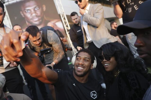 "Heavyweight boxer Anthony Joshua of Britain takes a selfie during a weigh-in at Faisaliah Center, in Riyadh, Saudi Arabia, Friday, Dec. 6, 2019. The first ever heavyweight title fight in the Middle East, has been called the ""Clash on the Dunes."" Will take place at the Diriyah Arena on Saturday. (AP Photo/Hassan Ammar)"