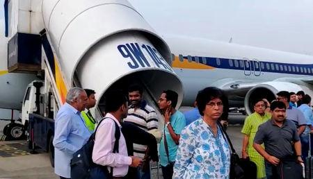 Passengers stand on the tarmac after an emergency landing, due to lost cabin pressure, on a Jet Airways flight, in Mumbai