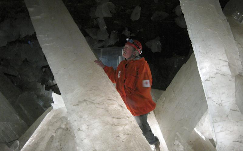 A researcher examines one of the giant crystals - Credit: Penelope J Boston/PA