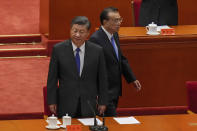 Chinese President Xi Jinping, left, and his Premier Li Keqiang arrive at an event commemorating the 110th anniversary of Xinhai Revolution at the Great Hall of the People in Beijing, Saturday, Oct. 9, 2021. Xi said on Saturday reunification with Taiwan must happen and will happen peacefully, despite a ratcheting-up of China's threats to attack the island. (AP Photo/Andy Wong)