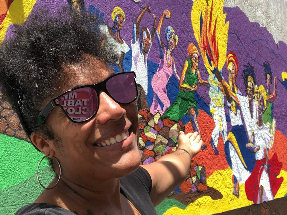 A woman taking a selfie points toward a mural on the street in Philipsburg.