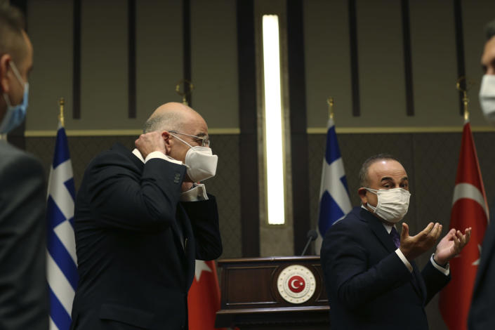 Turkish Foreign Minister Mevlut Cavusoglu, right, walks with Greek Foreign Minister Nikos Dendias, left following their joint media statement after their meeting in Ankara, Turkey, Thursday, April 15, 2021. Dendias travelled to Ankara for talks on the two NATO allies' fraught relationship, following a slight easing of tensions between the neighbors. The visit is the first between the two nations following a tumultuous year. (AP Photo/Burhan Ozbilici)