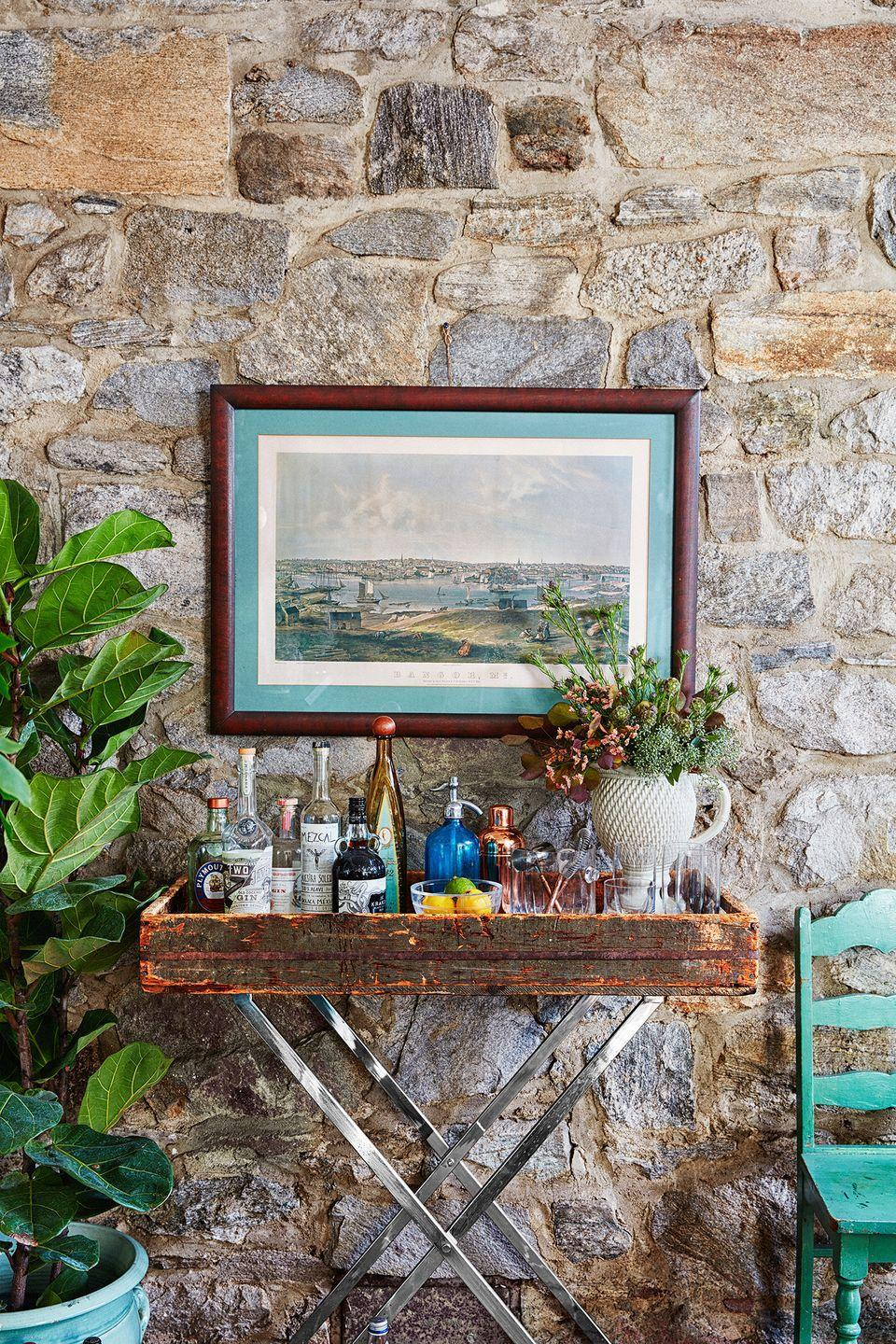 <p>If you're partial to a rustic aesthetic, turn a weathered wood tray into a bar cart for your go-to bottles and barware.</p>