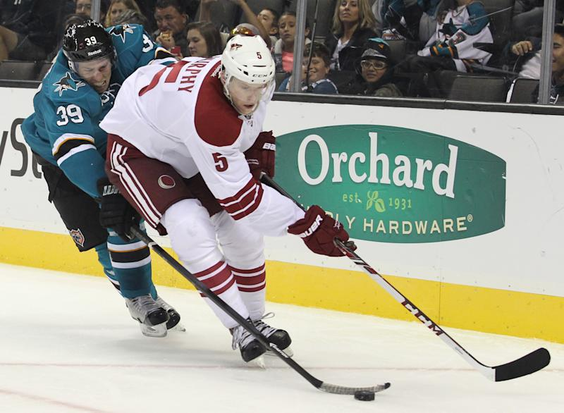 The Coyotes' Connor Murphy is chased by the Sharks' Logan Couture during an NHL preseason hockey game in San Jose, Calif., Saturday, Sept. 21, 2013. The Sharks won 3-2 in overtime. (AP Photo/Mathew Sumner)