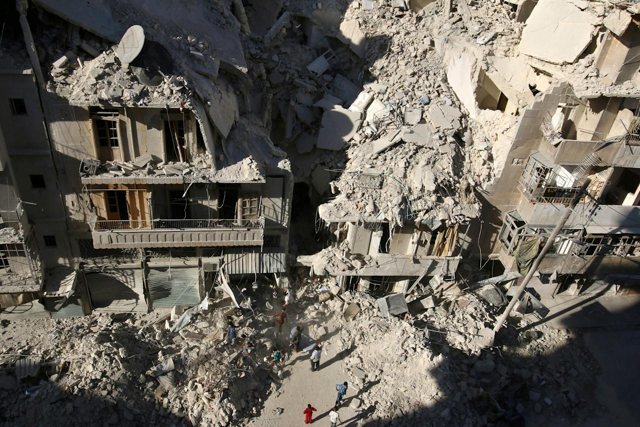 FILE PHOTO: People dig in the rubble in an ongoing search for survivors at a site hit previously by an airstrike in the rebel-held Tariq al-Bab neighborhood of Aleppo, Syria, September 26, 2016.   To match Special Report MIDEAST-CRISIS/IRAQ-NUJABA      REUTERS/Abdalrhman Ismail/File Photo