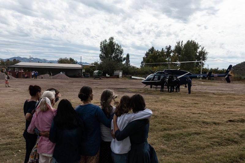 Family members watch a helicopter prepare to leave with the body of Christina Langford Johnson. | César Rodríguez—El País