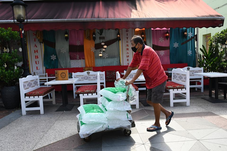 A man pushes a trolley load of ice to a restaurant in the Arab Street district. (PHOTO: Getty Images)