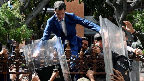 PHOTO: TVenezuelan opposition leader Juan Guaido is helped to climb a fence in an attempt to reach the National Assembly building in Caracas, on Jan. 5, 2020. Guaido and fellow opposition lawmakers were blocked from entering the National Assembly. (Federico Parra/AFP via Getty Images)