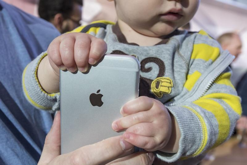Baby holding Apple iPhone
