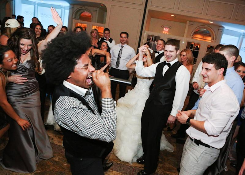 This Nov. 23, 2012 photo provided by Alana Mallon shows groom, Jim Mallon, second right, enjoying singer Gedeon McKinney and the Uptown Swing Band he hired through GMS Management for his wedding to his bride, Alana Mallon, during the reception in New Rochelle, New York. Generations ago, planning a wedding was 100 percent the bride's job, but in today's age of gender equity, it's a mere 99 percent. Modern men are more involved than ever. (AP Photo/Alana Mallon, Janie Algeri, VIP Events, LLC)