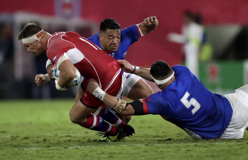 Russia's Dmitry Gerasimov is tackled by Samoa's Kane Le'aupepe, right, and Motu Matu'u during the Rugby World Cup Pool A game between Russia and Samoa at Kumagaya Rugby Stadium, Kumagaya City, Japan, Tuesday, Sept. 24, 2019. (AP Photo/Jae Hong)