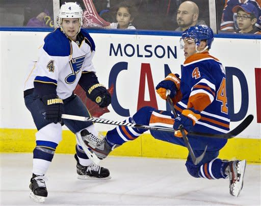 St. Louis Blues' Kris Russell, 4, checks Edmonton Oilers Taylor Hall, right, during first period NHL hockey action in Edmonton, Alberta, on Saturday March 23, 2013. (AP Photo/The Canadian Press, Jason Franson)