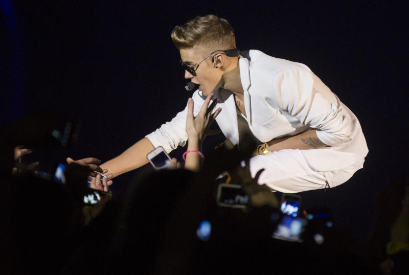 """Canadian singer Justin Bieber shakes hands with a fan as he performs on stage during the """"I Believe Tour """" in Berlin, Germany, Sunday, March 31, 2013. (AP Photo/Gero Breloer)"""