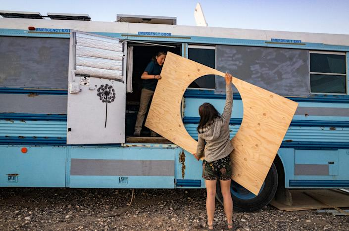 """Paula and Max carry in a piece of wood to mount around Max's """"hobbit bed"""" on the school bus, outside Ehrenberg, Az., on Feb. 8.<span class=""""copyright"""">Nina Riggio for TIME</span>"""