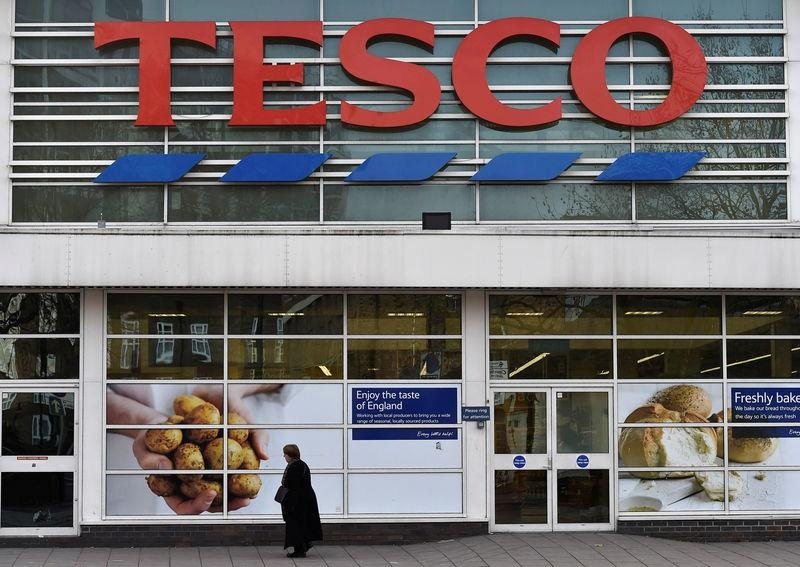 FILE PHOTO: A woman walks past a Tesco supermarket in central London