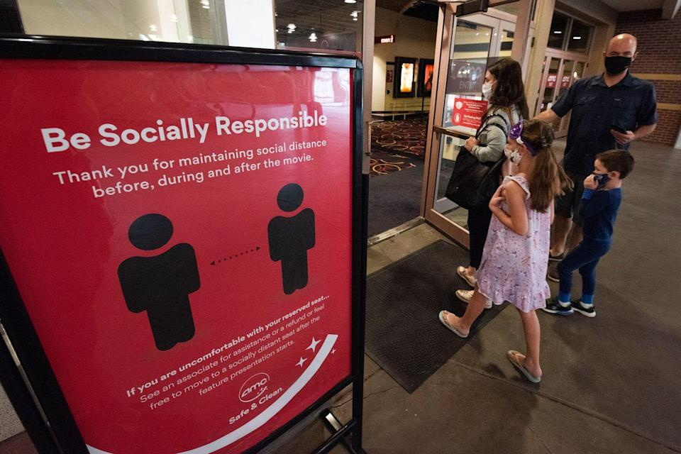<p>Movie goers enter the AMC Highlands Ranch 24 on August 20 in Highlands Ranch, Colorado.</p>
