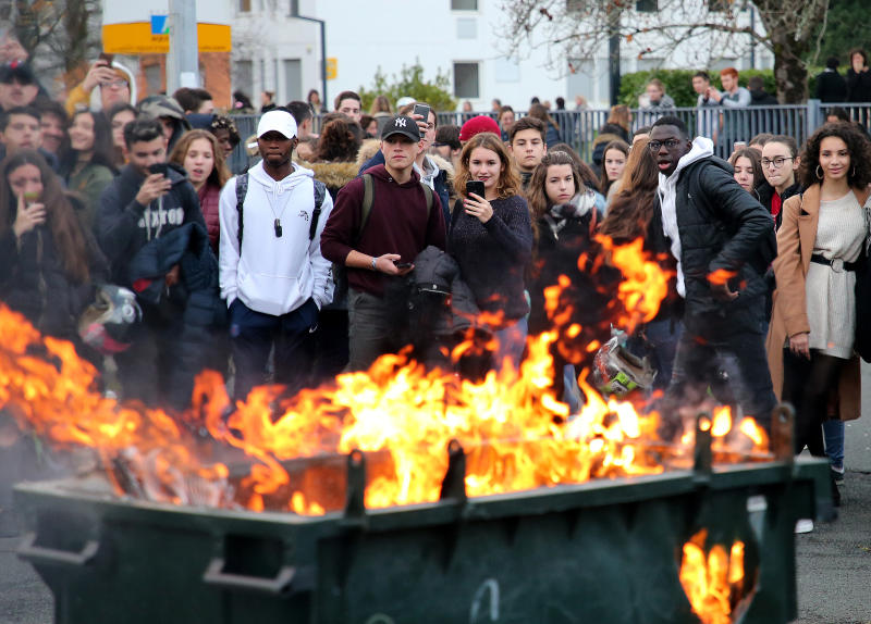 Students watch a burning trash bin outside their school in Bayonne, southwestern France, Thursday, Dec.6, 2018. Protesting students are disrupting schools and universities Thursday, and drivers are still blocking roads around France, now demanding broader tax cuts and government aid. (AP Photo/Bob Edme)